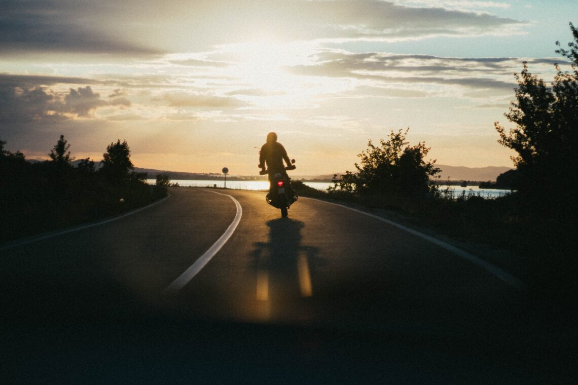 person riding motorcycle during golden hour
